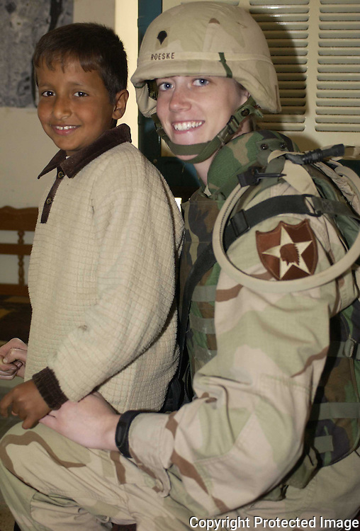 The author's friend and fellow unit 139 MPAD unit member Sara Roeske with an Iraqi boy.