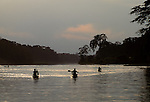 Silhouettes of native men paddling wooden dugout canoes on the calm waters of a narrow tributary of the Amazon River in Brazil with rainforest trees along the shores.