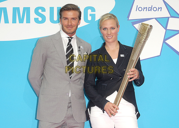 David Beckham & Zara Phillips.Samsung kicks-off its London 2012 campaign 'Everyone's Olympic Games', Canary Wharf, London, England..13th June 2011.half length grey gray suit jacket stubble beard facial hair torch gold blazer black white.CAP/BEL.©Tom Belcher/Capital Pictures.