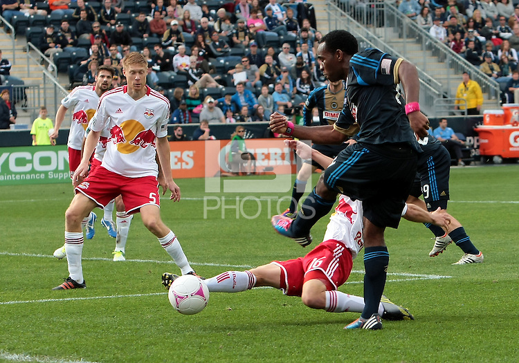 CHESTER, PA - OCTOBER 27, 2012:  Amobi Okugo (14) of the Philadelphia Union blasts the ball off  Connor Lade (16) of the New York Red Bulls during an MLS match at PPL Park in Chester, PA. on October 27. Red Bulls won 3-0.
