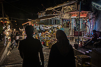 Teheran, coppia passeggia di sera in un mercato<br />