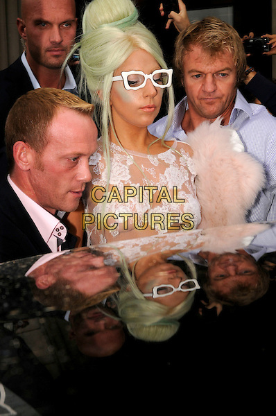 Lady Gaga (Stefani Joanne Angelina Germanotta).Leaving her hotel this morning, London, England..5th October 2011.half length security minders lace breasts cleavage boob reflection pink fur white glasses green highlights hair beehive bun profile side fan.CAP/IA.©Ian Allis/Capital Pictures.