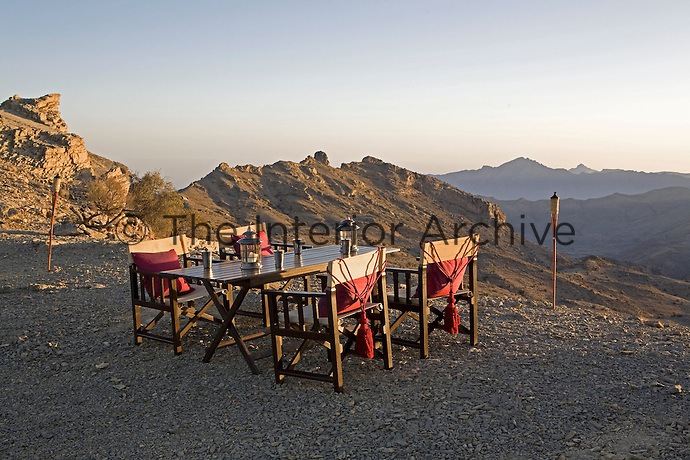 A wooden table and director's chairs make up the camp's mountain-top al fresco dining room