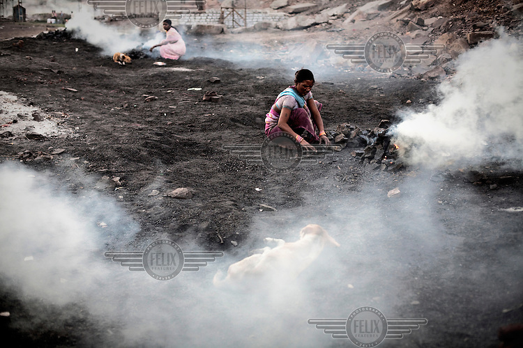 Residents of Bokapahari village burning piles of raw coal, processing it into charcoal. Coal fires rage just below the surface of the ground, making it too hot to walk with naked feet. Noxious gases spew up from fissures, rendering the environment toxic. Residents who live above the furnace make $2 a day collecting small chunks of coal that they sell to illegal middlemen. One or two houses collapse annually into vast underground caverns left unfilled by abandoned mining operations.