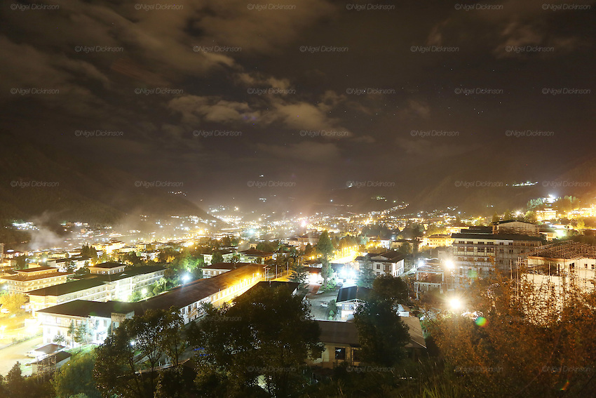 The capital of Bhutan, Thimpu at night..Bhutan the country that prides itself on the development of 'Gross National Happiness' rather than GNP. This attitude pervades education, government, proclamations by royalty and politicians alike, and in the daily life of Bhutanese people. Strong adherence and respect for a royal family and Buddhism, mean the people generally follow what they are told and taught. There are of course contradictions between the modern and tradional world more often seen in urban rather than rural contexts. Phallic images of huge penises adorn the traditional homes, surrounded by animal spirits; Gross National Penis. Slow development, and fending off the modern world, television only introduced ten years ago, the lack of intrusive tourism, as tourists need to pay a daily minimum entry of $250, ecotourism for the rich, leaves a relatively unworldly populace, but with very high literacy, good health service and payments to peasants to not kill wild animals, or misuse forest, enables sustainable development and protects the country's natural heritage. Whilst various hydro-electric schemes, cash crops including apples, pull in import revenue, and Bhutan is helped with aid from the international community. Its population is only a meagre 700,000. Indian and Nepalese workers carry out the menial road and construction work.