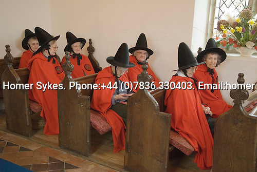 Old Ladies of Castle Rising. The Hospital of the Holy and Undivided Trinity Almshouses, Castle Rising, Norfolk, England 2007. Founders Day. The ladies wear tradiotional red cloaks and pointed black hats. Service in Chapel.
