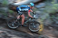 A woman competitor races her mountain bike down a narrow singletrack trail at the Lake Chelan Mountain Bike Festival in eastern Washington.