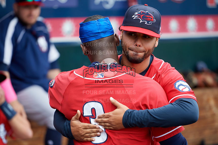 New Hampshire Fisher Cats coach Andy Fermin (2) hugs Jonathan Davis (3) in the dugout during the first game of a doubleheader against the Harrisburg Senators on May 13, 2018 at FNB Field in Harrisburg, Pennsylvania.  New Hampshire defeated Harrisburg 6-1.  (Mike Janes/Four Seam Images)