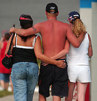 An race fan has his hands full and vice versa as he walks with two women through the infield at Daytona International Speedway Saturday afternoon.