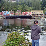 man fishes in Ketchikan harbor, Alaska on a rainy August morning, Creek Street in background