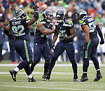 Seattle Seahawks defensive unit celebrates a sack by defensive end Cliff Avril (56) against the Denver Broncos during the first quarter at CenturyLink Field on August 14, 2015 in Seattle Washington.  The Broncos beat the Seahawks 22-20.  © 2015. Jim Bryant Photo. All Rights Reserved.