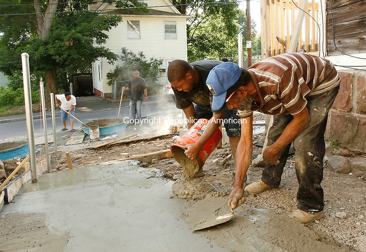 WATERBURY, CT 07/05/09- 070509BZ04- Terrell Moore dumps a 5-gallon bucket of concrete into a form as Herman Chapman trowels it out while pouring a new concrete driveway on Bishop Street in Waterbury Sunday afternoon. In the background, neighbor Ronald Barnes and homeowner Charles Johnson mix concrete in a child's swimming pool turned mixing bowl. <br /> Johnson said the pool allowed them to mix more concrete to cover the large area of the driveway and that they had used 18 bags of Quikrete for the job so far.  The project was teaching his kids &quot;substance&quot; (life skills and work ethic) while also maintaining his property, he said.  &quot;You don't want to finish paying for something and have a junk pile,&quot; he said.<br /> Jamison C. Bazinet Republican-American