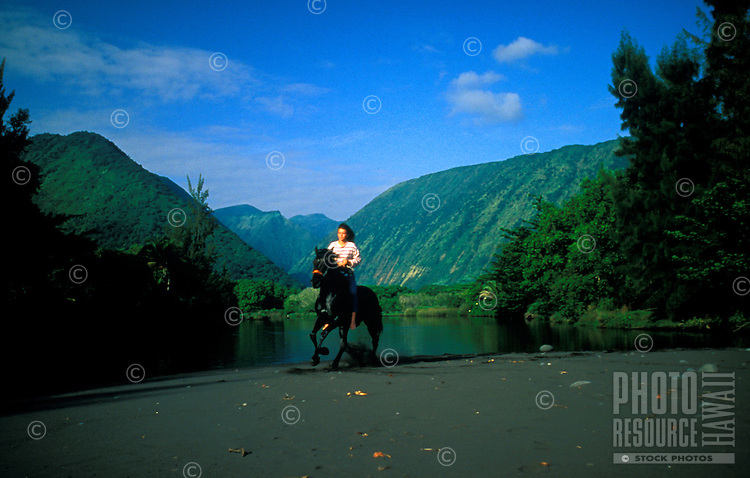 A woman enjoy a horseback ride on the black sand beach in Waipio Valley on the Big island