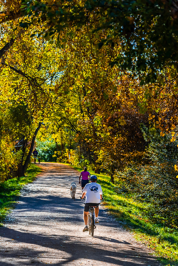 People bicycling on the Highline Canal path on an Autumn afternoon, Littleton, Colorado USA.