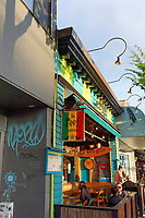 People sitting and chatting outside The Reef Caribbean food restaurant on Main Street in Vancouver, BC, Canada