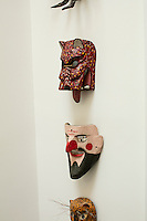 A collection of carnival masks are displayed on the wall.
