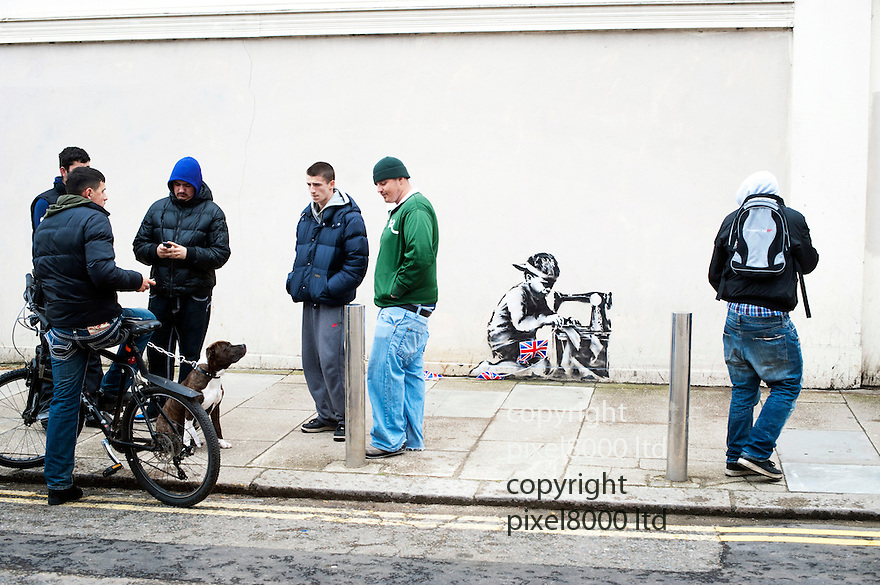 "Latest work believe to be by mysteriious graffiti artist Banksy ..It is  in Turnpike Lane London and painted on the wall of bargain store Poundland with an image depicting a child making Jubilee street party bunting in a sweatshop...The Banksy image depicts a young boy crouched over a sewing machine. The Jubilee-themed artwork has Union flag bunting similar to that sold in the store hung across the image...Some ""enterprising"" local lads were asking for £5 from photographers to get a snap of the work. But once refused eventually gave up and moved out of the way.....Picture by Gavin Rodgers/ Pixel8000. 07917221968"