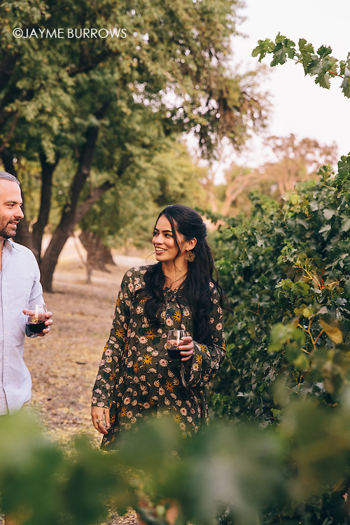 Couple walking through a California vineyard.