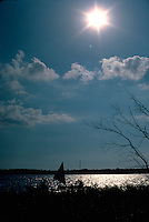 Silhouette of friends age 15 in a canoe rigged for sailing.  Clitherall Minnesota USA