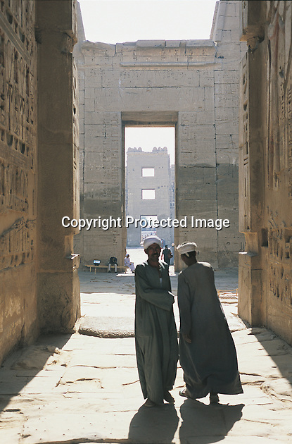 Two men converse at the entrance to the hypostyle hall in Medinat Habu, with the main gateway into the walled city in the far background. This city was built as a power base by Ramses III, the last of the great Pharoahs of Egypt, during his reign from 1184 to 1153BC.
