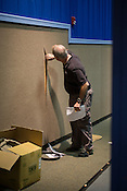 Tom Schroeder checks the walls of the theater for sound-proofing materials, Galaxy Cinema, Cary, Sat., Jan. 12, 2013.