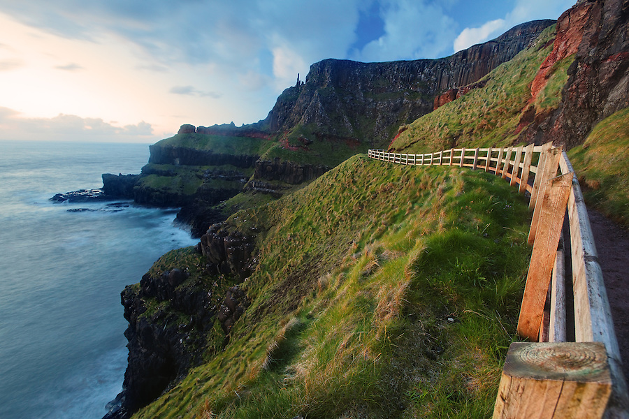Fenced cliffside trail on Benbane Head near sunset, Giant's Causeway, County Antrim, Northern Ireland, United Kingdom