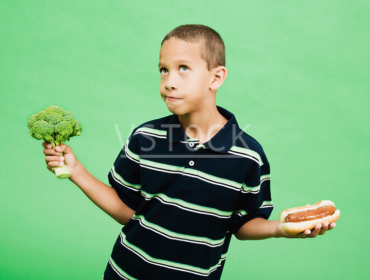 Boy (8-10) holding broccoli and hotdog, studio shot