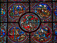 Medieval stained glass Window of the Gothic Cathedral of Chartres, France - dedicated to the Life of St Lubin . Central panel shows A barrel of wine being transported to the Cathedral, below left - The young Lubin working as a shepherd, below right - A monk gives Lubin a belt with the alphabet written on it, above left - Lubin receiving instruction from a cleric, above right - Lubin spends his spare time learning to read, while his companion idles.  A UNESCO World Heritage Site..