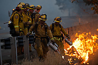 Firefighters use drip torches to burn excess brush, creating a wide fire break along US Route 50 near the town of Pollock Pines, California, USA, on 18 September 2014. Fire crews around California fight 12 major fires across the state, including the King Fire, located 56 miles (90 kilometers) east of Sacramento, California, which more than doubled in size overnight to 70,994 acres (28,730 hectares) and 5% contained.