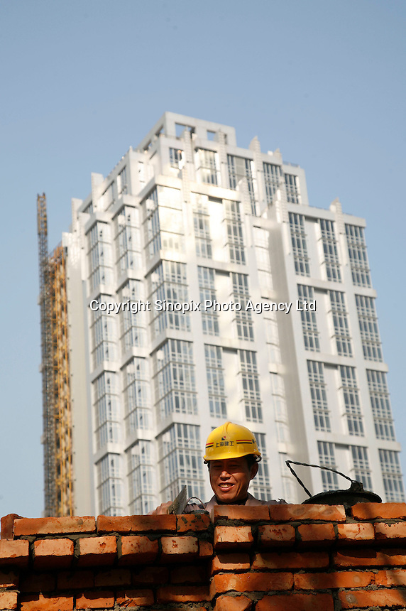 A worker builds a wall around a new construction site in Shanghai, China..