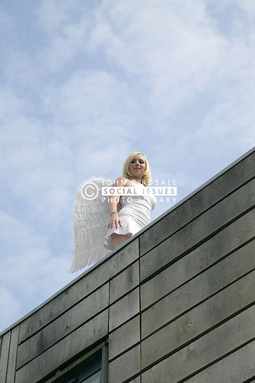 Woman modelling for a photo shoot on a roof top,