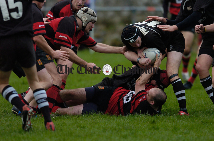 A fallen Declan Ryan of Ennis is robbed of the ball by his Cobh Pirates opponedt as team mate Mike Reid moves in during their game at Ennis RFC on Saturday. Photograph by John Kelly.