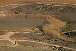 Israel, Coastal Plain, a bike rider at the foothill of Tel Nagila