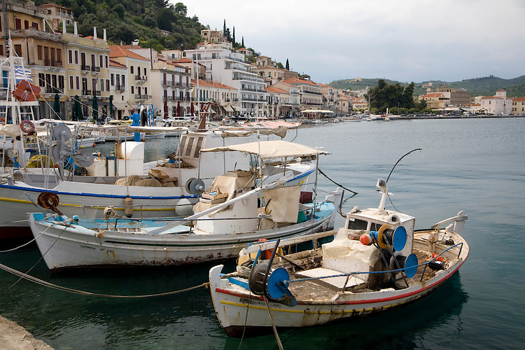 The seaport of Githio, Greece forms a colorful pallete of brightly colored fishing boats backdropped with the town's buildings clustered between the harbor and the surrounding hills.