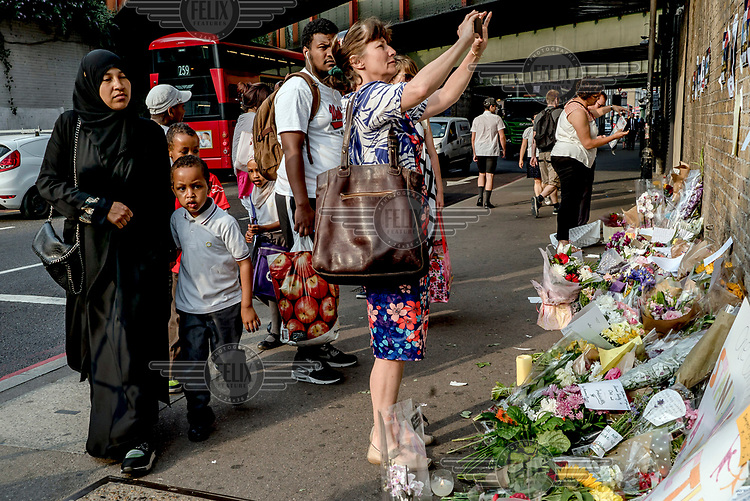 A woman stops to take a picture as others pass by a memorial of flowers left to honour the victims of the 19 June 2017  Finsbury Park mosque terrorist attack.