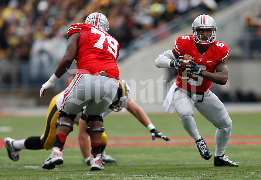 Ohio State Buckeyes quarterback Braxton Miller (5) runs through a hole blocked by Ohio State Buckeyes offensive linesman Marcus Hall (79) in the second quarter the NCAA football game between the Ohio State Buckeyes and the Iowa Hawkeyes at Ohio Stadium in Columbus, Saturday afternoon, October 19, 2013. The Ohio State Buckeyes defeated the Iowa Hawkeyes 34 - 24.  (The Columbus Dispatch / Eamon Queeney)