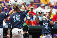 North Carolina catcher Brian Holberton (10) is greeted at the plate by teammate Colin Moran (18) after he hit a 3 run home run in the first inning against the Louisiana State Tigers during Game 7 of the 2013 Men's College World Series on June 18, 2013 at TD Ameritrade Park in Omaha, Nebraska. The Tar Heels defeated the Tigers 4-2, eliminating LSU from the tournament. (Andrew Woolley/Four Seam Images)