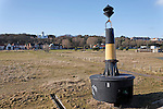 Navigation beacon marker. Looking inshore to the lighthouse over area formerly used by herring fishing industry, Lowestoft, Suffolk, England