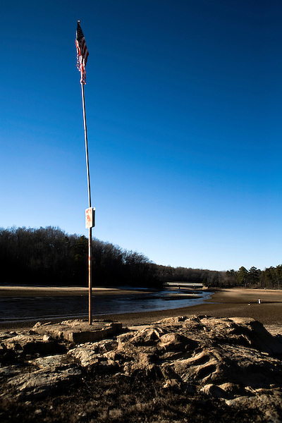 """January 21, 2008. Bahama, NC.. Photos of Lake Michie, the main reservoir for the city of Durham, NC. .The drought crisis in the Durham area has reached the """"critical"""" level, with an estimated 119 days of easily accessible drinking water remaining.. A US flag sits in the dry river bed of the main Durham reservoir."""