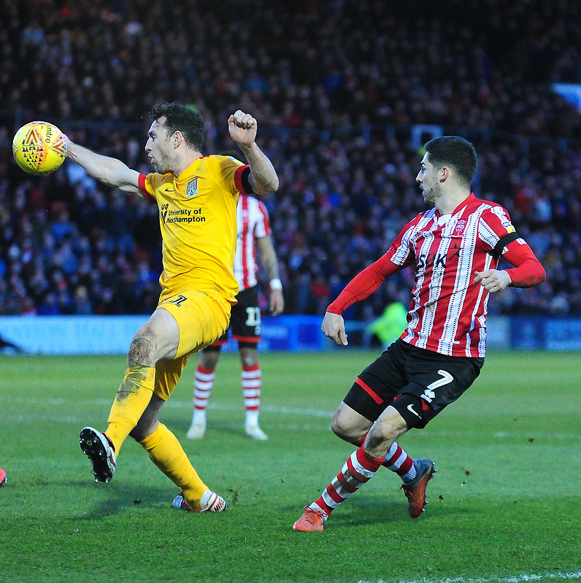Northampton Town's John-Joe O'Toole appears to handle a cross from Lincoln City's Tom Pett<br /> <br /> Photographer Andrew Vaughan/CameraSport<br /> <br /> The EFL Sky Bet League Two - Lincoln City v Northampton Town - Saturday 9th February 2019 - Sincil Bank - Lincoln<br /> <br /> World Copyright © 2019 CameraSport. All rights reserved. 43 Linden Ave. Countesthorpe. Leicester. England. LE8 5PG - Tel: +44 (0) 116 277 4147 - admin@camerasport.com - www.camerasport.com