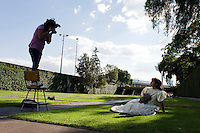 A photography student sets-up a mock quicañera (sweet 15)portrait session with a friend. The Mexico City campus (Ciudad Universitario) of the UNAM (Universidad Autonomo de Mexico) Mexico City. June 20, 2008