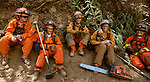 Women firefighters from the Rainbow Crew of the California Department of Corrections take a short break after cleaning up a hot spot on Montgomery Ridge, Division S, Old Yosemite Road, to protect the Greeley Hill community.