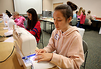 NWA Democrat-Gazette/DAVID GOTTSCHALK  Kim Andrade puts in a 3/8th inch stitch Tuesday, March 20, 2018, during the first session of the Sewing Club Workshop at the Springdale Public Library. Participants, ages 10-14, in the two day workshop are making are learning the use of a sewing machine and fabric techniques as they make a pillowcase and an overnight bag.