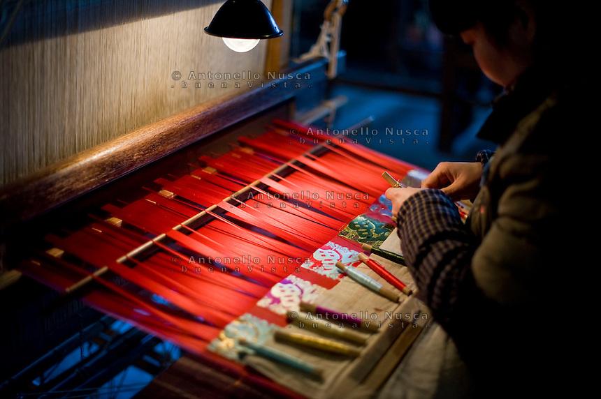 Una donna durante una fase di lavorazione della seta in una vecchia fabbrica.<br /> Wuzhen &egrave; una piccola citt&agrave; della provincia dello Zhejiang chiamata anche la Venezia d'Oriente per la caratteristica dei canali che corrono lungo i vicoli dell'antica citt&agrave;. E' anche riconosciuta come uno dei centri pi&ugrave; importanti per la produzione e la lavorazione della seta nell'antichit&agrave;. Ancora sono presenti alcune piccole ditte che continuano a lavorare la seta con gli stessi metodi di come si faceva da secoli. Nonostante sia diventata una meta turistica ancora si pu&ograve; respirare la vecchia Cina passeggiando tra i vecchi vicoli costruiti con la pietra e rimasti intatti nei secoli.