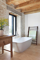 In one coner of the bedroom is a free-standing bath tub, stood below a window for views onto the surrounding countryside
