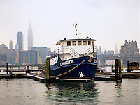 Angela Lindwall's houseboat, the Lakota, moored with the grey New York city skyline in the background