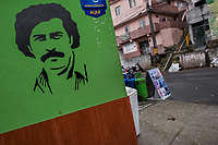 "A portrait artwork, depicting the drug lord Pablo Escobar, is seen painted on the corner in the Pablo Escobar neighborhood in Medellín, Colombia, 30 November 2017. Twenty five years after Pablo Escobar's death, the legacy of the Medellín Cartel leader is alive and flourishing. Although many Colombians who lived through the decades of drug wars, assassinations, kidnappings, reject Pablo Escobar's cult and his celebrity status, there is a significant number of Colombians who admire him, worshipping the questionable ""Robin Hood"" image he had. Moreover, in the recent years, the popular ""Narcos"" TV series has inspired thousands of tourists to visit Medellín, creating a booming business for many but causing a controversial rise of narco-tourism."