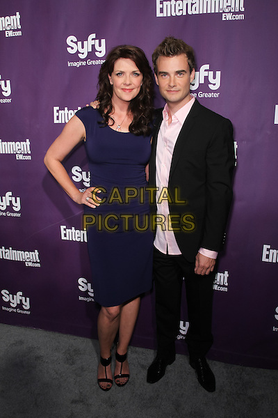 AMANDA TAPPING, ROBIN DUNNE.At the annual Entertainment Weekly and Syfy Party in conjunction with Comic-Con 2010 at the Hotel Solamar, San Diego, CA, USA,.July 24th 2010..full length blue navy dress black suit hand on hip .CAP/CEL. ©CelPh/Capital Pictures