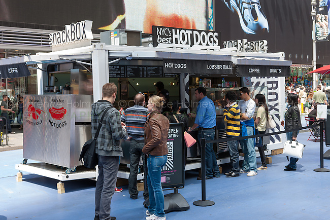 People stand in line to purchase street food at the Snack Box, a street vendor operating from a converted shipping container in Times Square in New York City