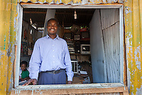 """Jared Orondo, 28, repairs electronics from his hole-in-the-wall shop in Nairobi's Kibera slum. """"I can save $10 a month and at year's end maybe buy new tools. Getting a loan from the bank is too expensive""""."""
